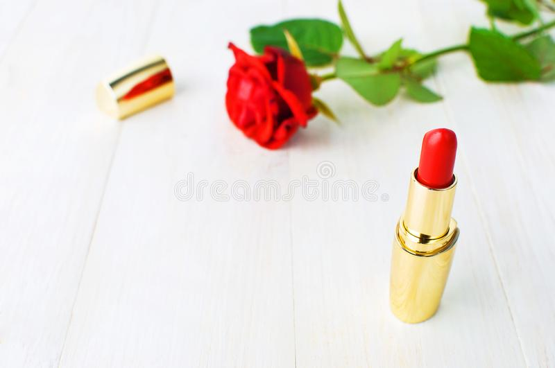 Red lipstick with red roses on pink background with copy space. Makeup Accessories Top view Flat Lay. Various cosmetic products fo royalty free stock photography