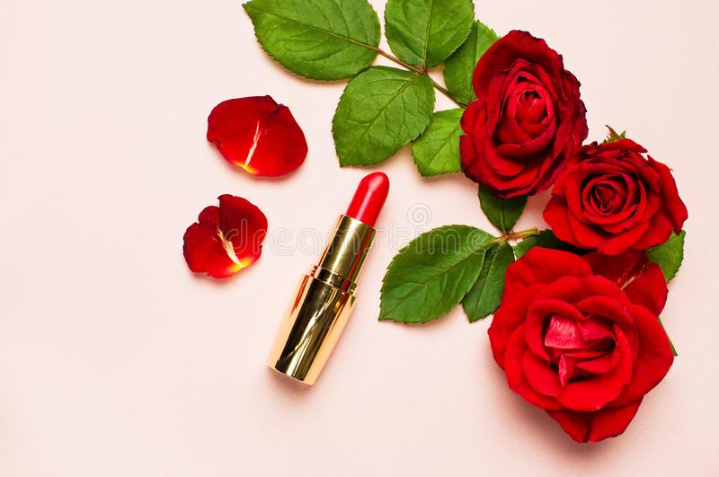 Red lipstick with red roses on pink background with copy space. Makeup Accessories Top view Flat Lay. Various cosmetic products fo stock images