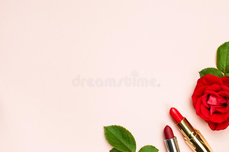 Red lipstick with red roses on pink background with copy space. Makeup Accessories Top view Flat Lay. Various cosmetic products fo royalty free stock photo
