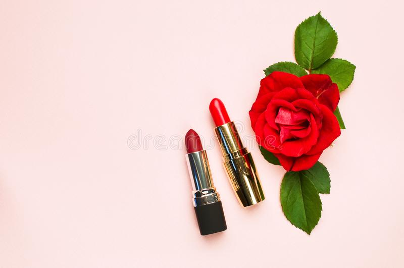 Red lipstick with red roses on pink background with copy space. Makeup Accessories Top view Flat Lay. Various cosmetic products fo stock photos