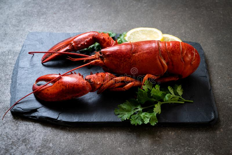 Lobster with vegetable and lemon on black slate plate. Red lobster with vegetable and lemon on black slate plate royalty free stock photography