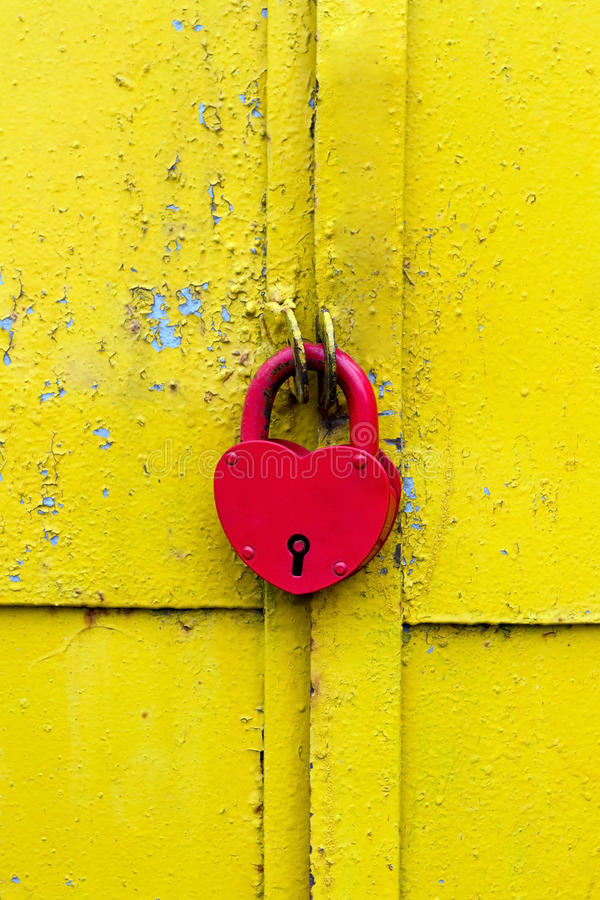 Red lock on a rusty yellow door stock images