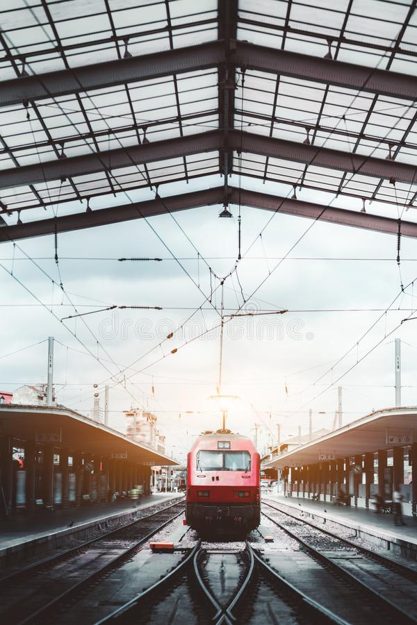 Red locomotive on a railway station. Vertical symmetrical shot of a railroad station depot with a triangle roof above, a modern red train locomotive being on stock image