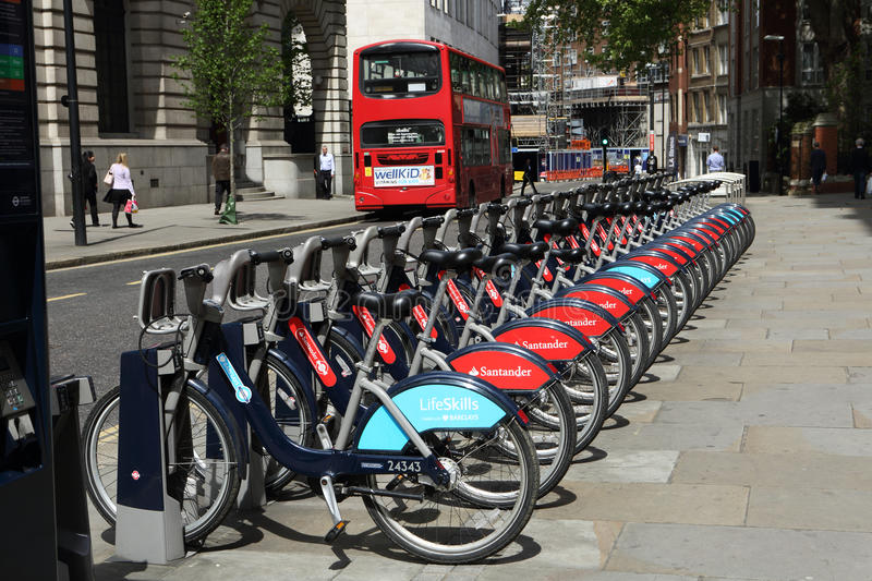 Red London double-decker bus and boris bikes. Red London double-decker bus on the city street and row of public transport for London self-service cycle-hire royalty free stock images