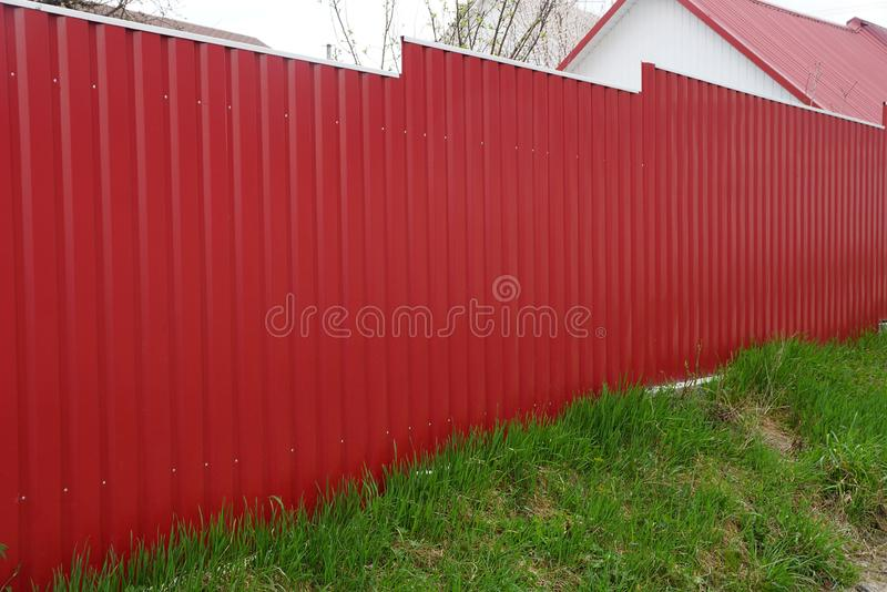 Red long metal fence outside in green grass stock photo