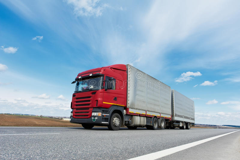 Red lorry with grey trailer over blue sky. Single red lorry truck with grey trailer over blue sky on the road royalty free stock image