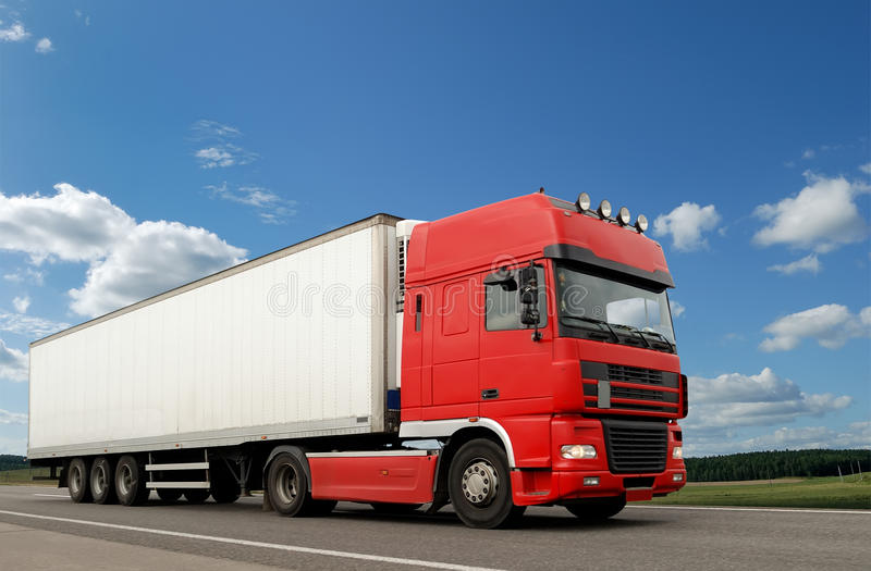 Red lorry with white trailer over blue sky. Single red lorry with white trailer over blue sky on the road. See other vans and trucks in my portfolio royalty free stock photography