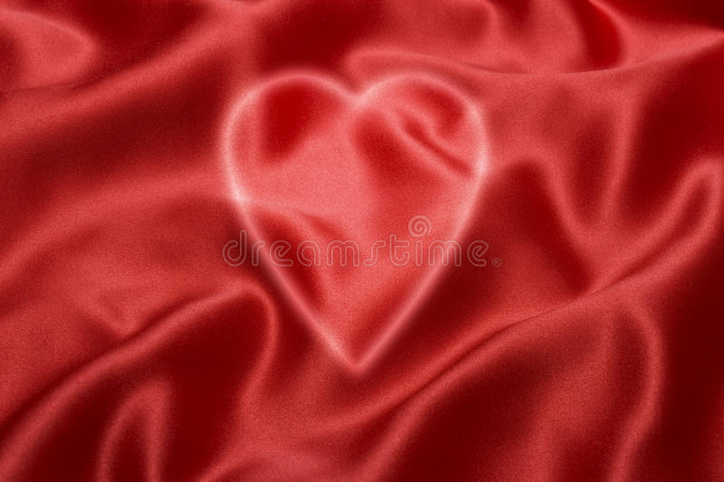 Red Love Heart Background. A love heart shape on a red satin background royalty free stock image