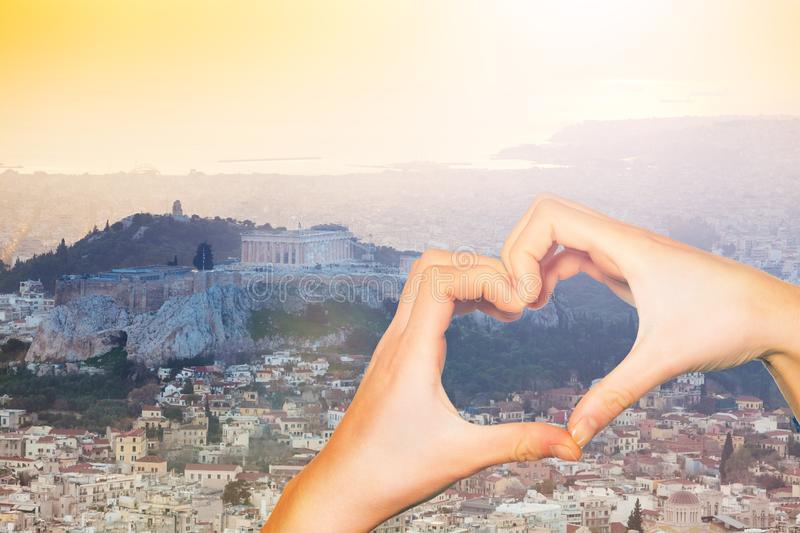 Hand hold red heart over sunset in Athens, Greece stock image