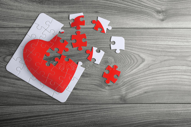 Red love heart puzzle with loose pieces. Red love heart puzzle with loose corner pieces stock images
