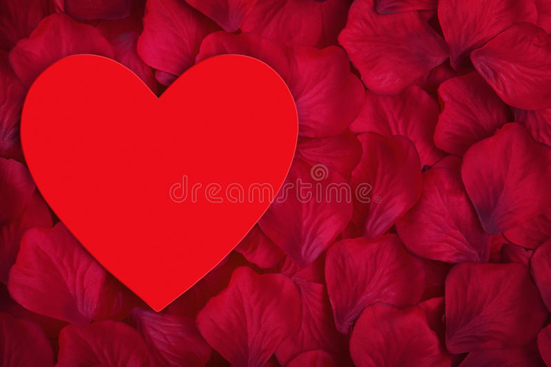 Red love heart with space for copy in the center. Red love heart with space for copy on red fabric rose petals stock photography