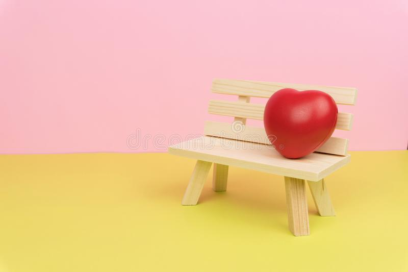 A red love heart symbol on the wooden bench royalty free stock photography