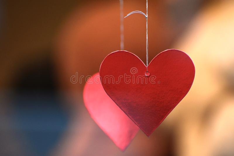Red Love Hearts hanging in a window. Two red love heart decorations hanging in a shop window leading up to Valentine`s Day 2019 royalty free stock image