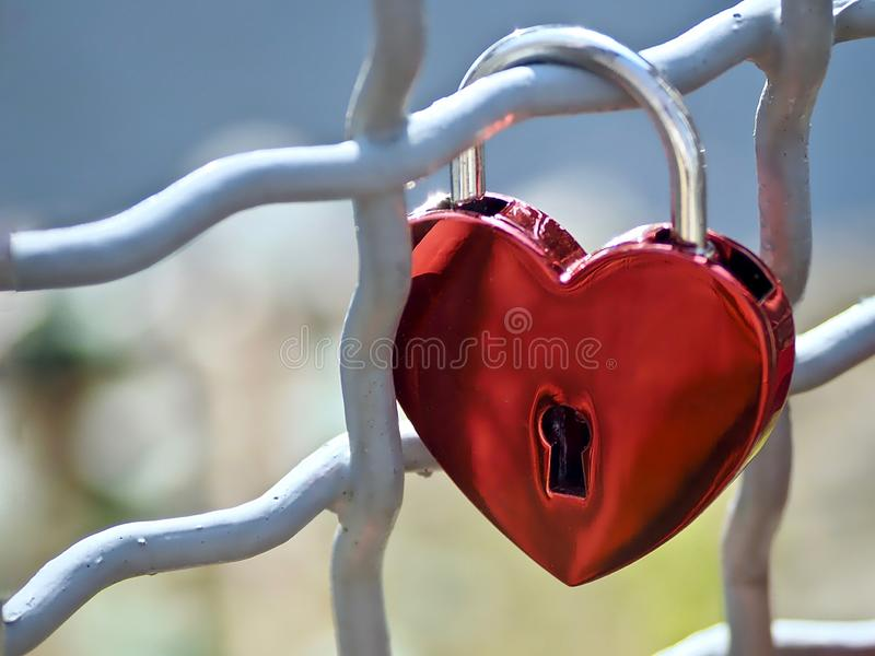 Red love lock in form of a heart. Red love lock at a fence in form of a heart royalty free stock photos