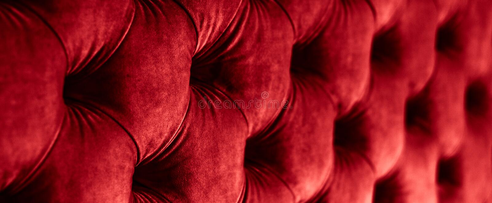 Red luxury velour quilted sofa upholstery with buttons, elegant home decor texture and background. Furniture design, classic interior and royal vintage material stock photo