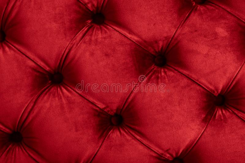 Red luxury velour quilted sofa upholstery with buttons, elegant home decor texture and background. Furniture design, classic interior and royal vintage material royalty free stock images