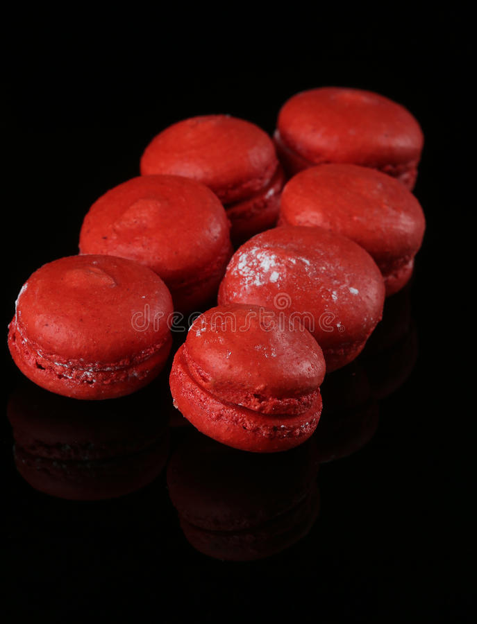 Red macaroons on black surface royalty free stock images