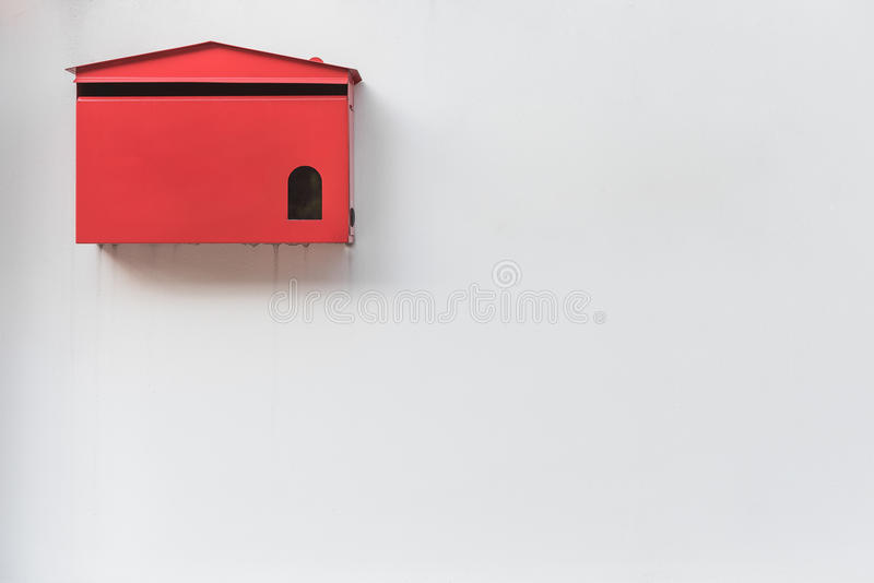 Red mailbox on old white wall royalty free stock photo