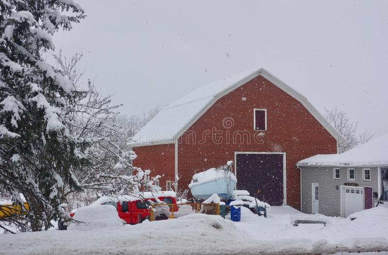 Red Maine barn in winter snowstorm stock image