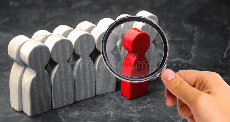 Red man coming out of the crowd. The chosen person among others. A talented worker. Promotion. Concept of search for a worker. The royalty free stock images