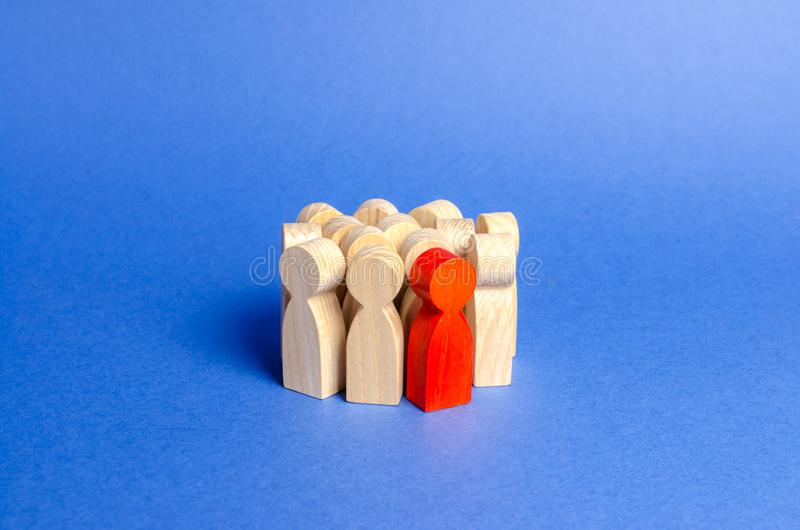 A red man stands in a crowd of people. Society, social group. management of people. Leadership qualities, talented employee. HR. Is looking for new employees royalty free stock photos