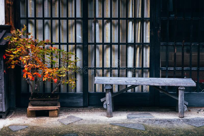 Red maple tree and old wooden bench outside japanese house. Vintage style royalty free stock photo