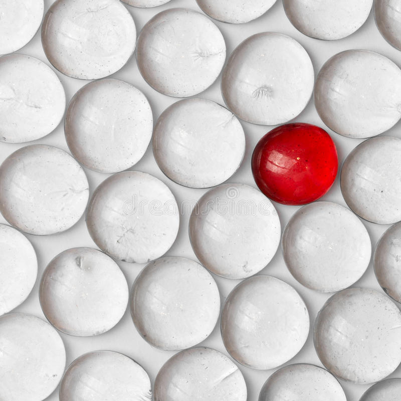 A red marble in a crowd of white marbles stock photo