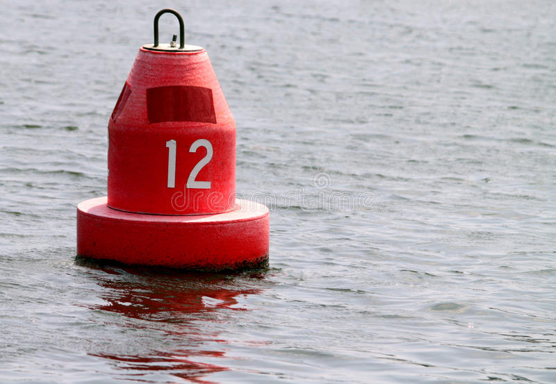 Red marker buoy. With a the number twelve on it stock image