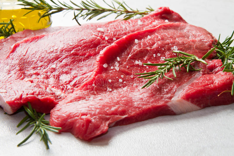Red meat. A red meat with rosemary on marble table royalty free stock photography