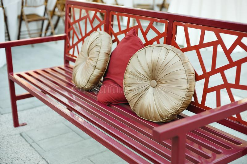 Red oriental inspired bench with pillows. A red metal bench with asian geometric design and festive pillows royalty free stock photography