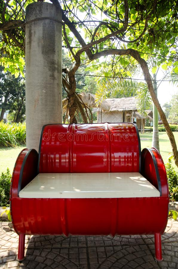 Red metal bench decoration and furniture in public garden park made from gas oil iron tank royalty free stock photography