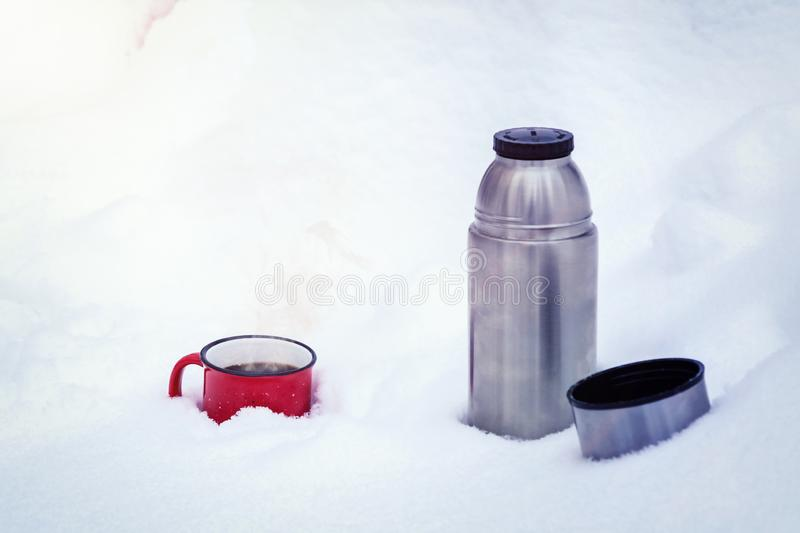 Red metal cup with coffee poured from a thermos on pure white snow in the forest while walking royalty free stock image