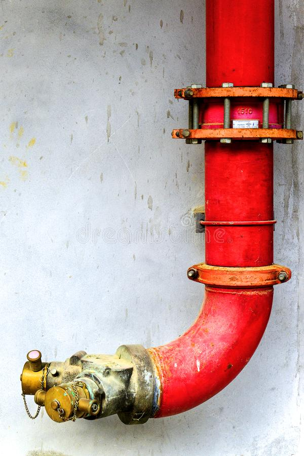 Red metal pipe extinguishing water on concrete wall. Emergency fire valve or Y shape hose tube in the building. Safety equipment a stock photo