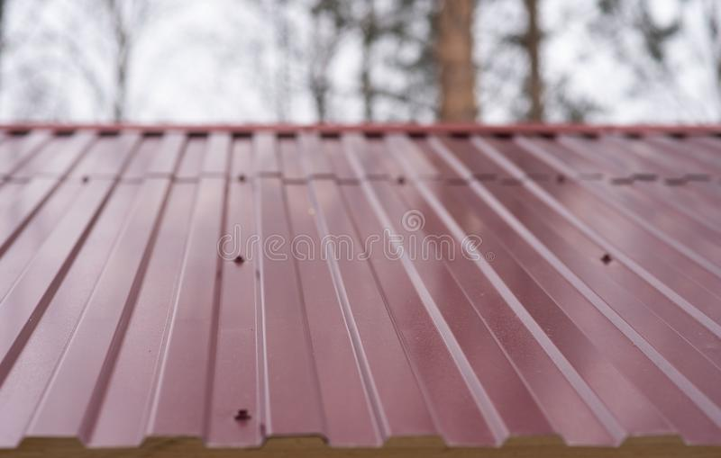 Fragment of the metal roof of the house. Red roof royalty free stock image