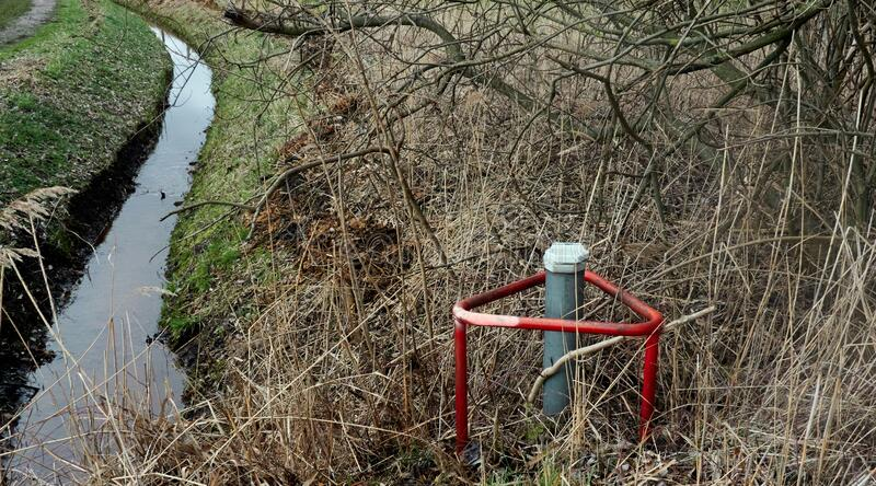Red metal stand in a grassy field with a lot of bushes near a ditch. A red metal stand in a grassy field with a lot of bushes near a ditch stock photography