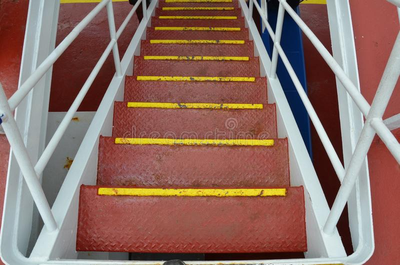 Red metal steps or stairs with railing on ship stock photography
