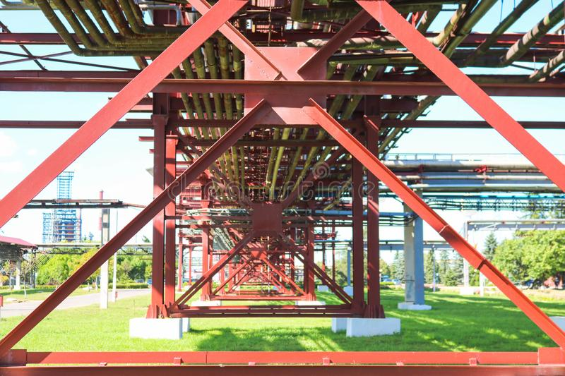 Red metal structures, wheel supports for pipes, pipeline trestle from large beams, piles and stiffeners at the oil refinery stock photos