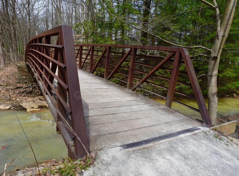 Red metal and wooden bridge over a creek in a forest. stock images
