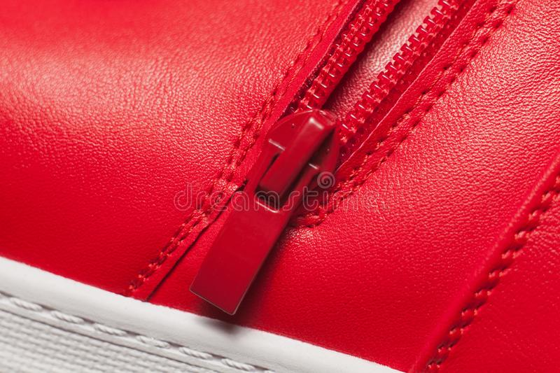 Red metal zipper on red sport boots royalty free stock images