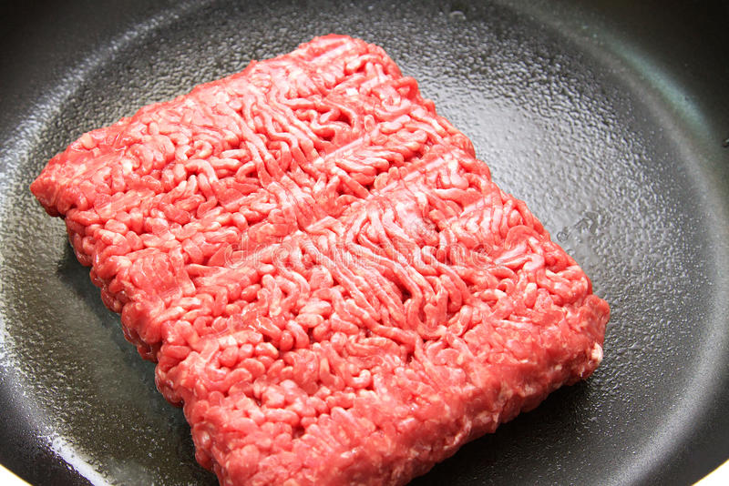 Red mince in pan. Fresh beef mince in a frying pan ready for cooking stock photos