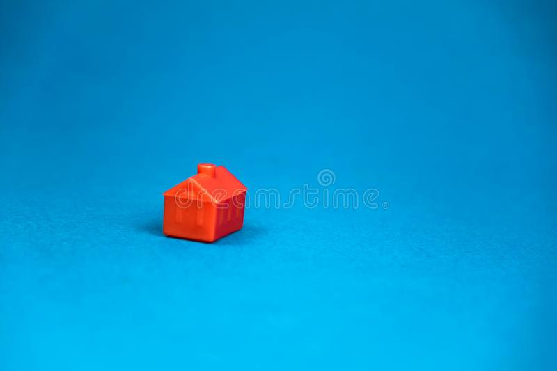 Red miniature lonely house standing on a blue background. Concept, model, successful, housing, luck, construction, business, car, design, hand, man, birthday stock photos
