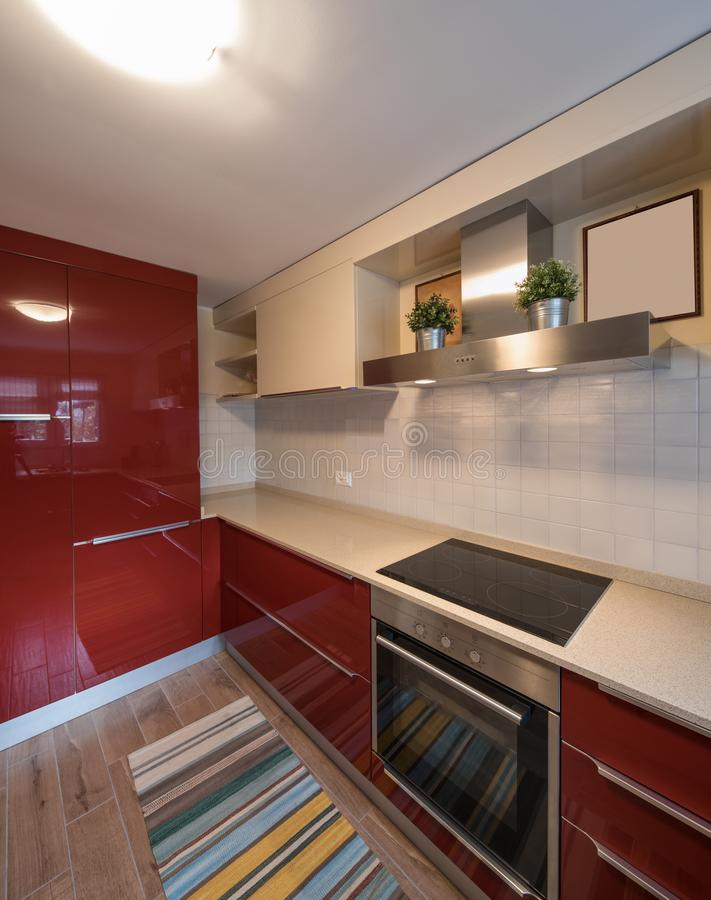 Red modern kitchen with new appliances. In the corner. Nobody inside stock photography