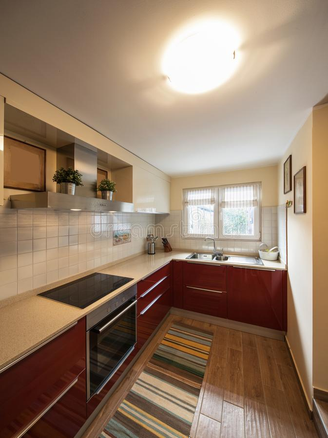 Red modern kitchen with new appliances. Nobody inside stock photo