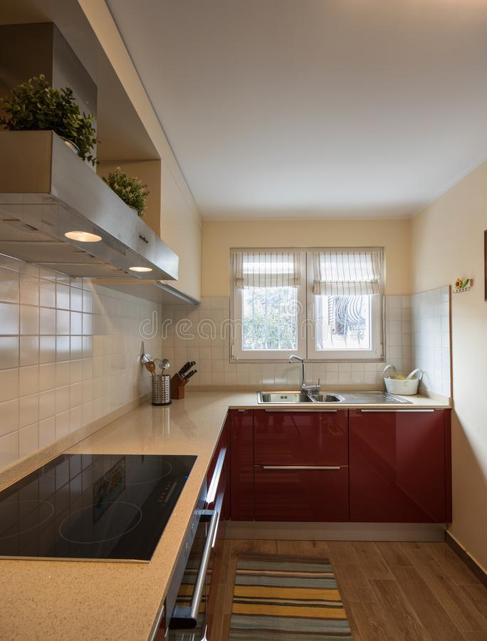 Red modern kitchen with new appliances. Nobody inside, close up stock photo