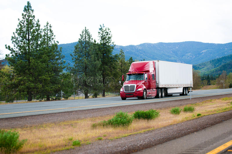 Red modern semi truck with dry van trailer moving by divided highway I-5 in California. Red big rig modern shiny semi-truck with white dry van trailer with stock images