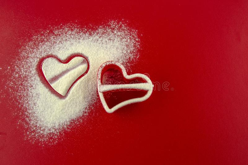 Red mold in the shape of bunnies sprinkled flour on red background royalty free stock photos