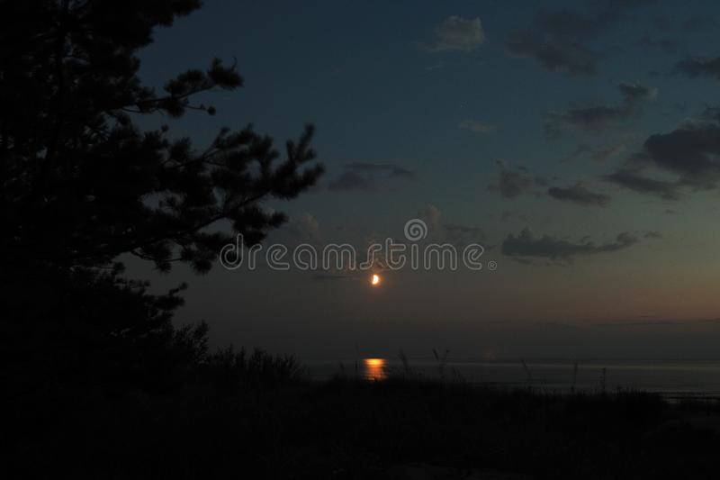 Moon lights and clouds after sunset royalty free stock photography