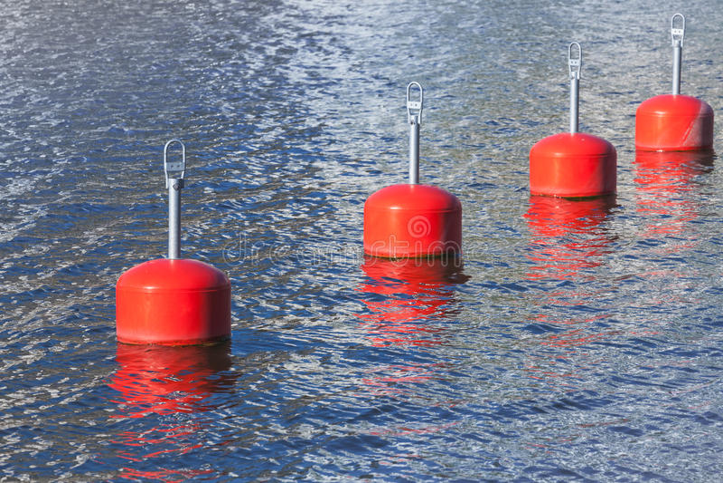 Red mooring buoys in a row, European marina. Nautical equipment royalty free stock photography