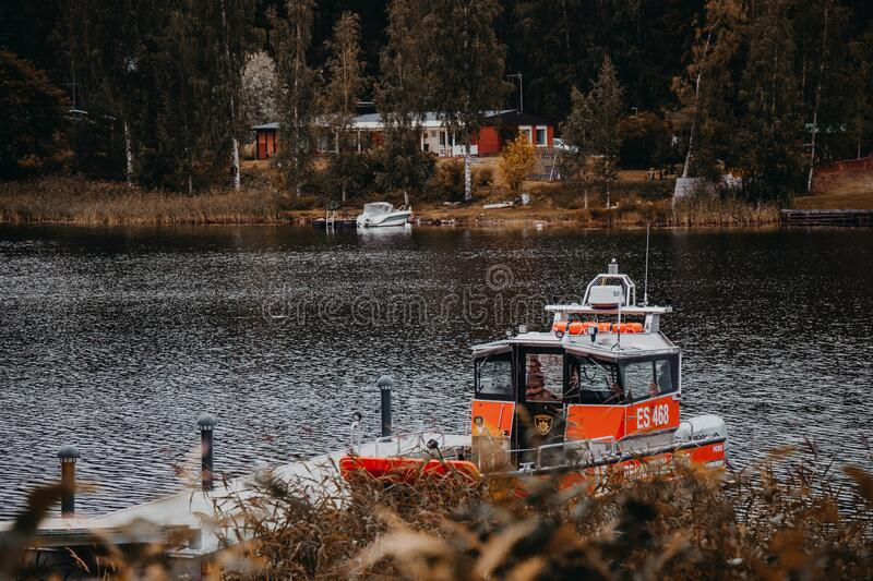 Red motorboat on lake pier near cone forest and buildings. royalty free stock photo