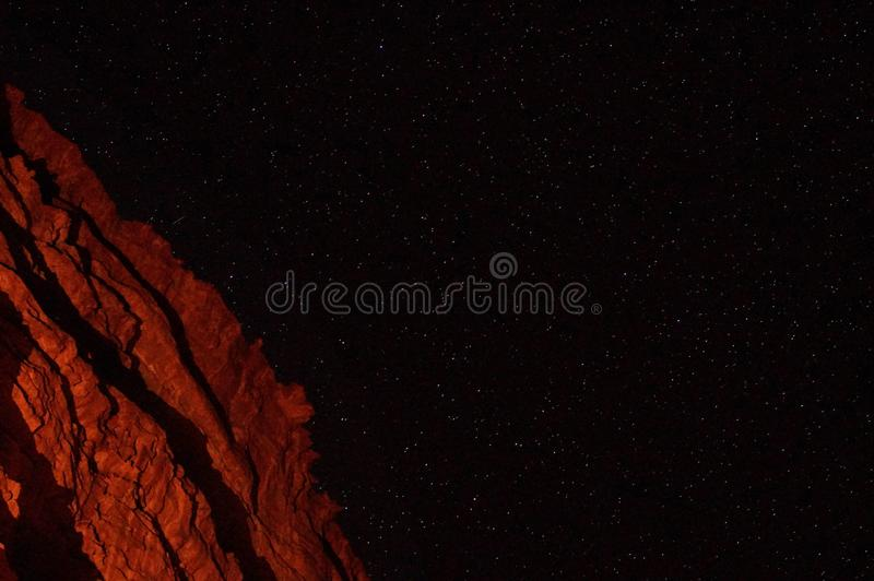 Red mountain in the desert at night with bright stars royalty free stock images